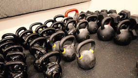 Black kettlebells in the fitness center or gym. Small to big and heavy. It`s a 4K video and a top view stock video