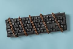 Black keyboard with a coiled chain. Concept for the topic of censorship or freedom of the press. Black keyboard with a coiled chain. Idea and concept for the royalty free stock images