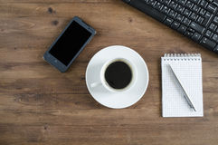 Black  keyboard, smart phone and office supplies Royalty Free Stock Image