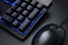 Black keyboard and wired mouse. Black keyboard numeric keys and wired mouse on the dark office desk royalty free stock photos