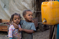 Black kid beside of canister Stock Photos
