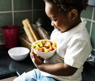 Black kid with fruit salad in the kitchen stock photo