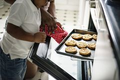 Black kid helping mom baking cookies in the kitchen Stock Photo