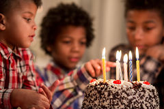 Black kid touching cake's candle. Royalty Free Stock Photography