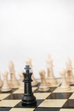 Black king against white figures in the chess Stock Images