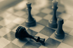 Black king is checkmated and fallen on chessboard Royalty Free Stock Images