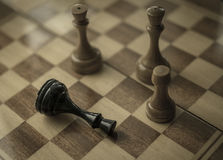 Black king is checkmated and fallen on chessboard Royalty Free Stock Image