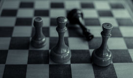 Black king is checkmated and fallen on chessboard Royalty Free Stock Photos
