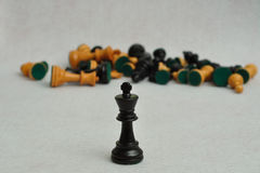 A black king in focus with the rest of the chess pieces Stock Photo
