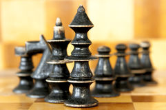 Black king gang. Chess black king with his  suite on chess board background Royalty Free Stock Photo
