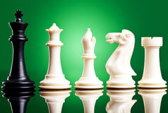 Black king near white chess pieces Stock Photo