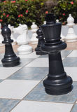 Black king in outdoor chess set in garden. Close up of large black king piece in outdoor chess set in flower garden Royalty Free Stock Photos