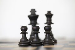 Black king and queen chess pieces with pawns Royalty Free Stock Photography