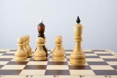 Black king surrounded by white pawns Royalty Free Stock Photography
