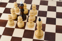 Black king surrounded by white pawns Stock Photo