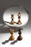 A black king and white queen is looking in a mirror to see themselves as a black and white colored couple. A pair of a black king and a white queen chess pieces Royalty Free Stock Image