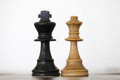 Black king and white queen wooden chess pieces. On chess board Royalty Free Stock Image