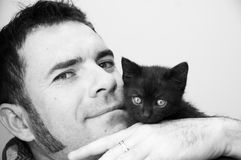 Black kitten with a guy Royalty Free Stock Images