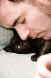 Black kitten with a guy Stock Image