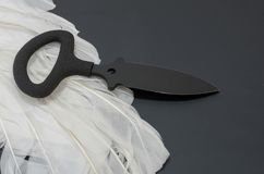 Black knife and white bird feathers. Good and evil. Back side. Royalty Free Stock Photo