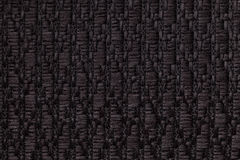 Black knitted woolen background with a pattern of soft, fleecy cloth. Texture of textile closeup. Royalty Free Stock Photography