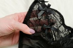 Black lace bodice in female hand. Close up.  Stock Photo