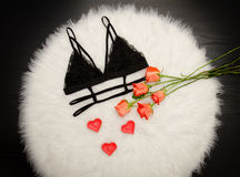 Black lace bra on white fur and a bouquet of orange roses. Fashionable concept. Top view Stock Photography