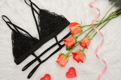 Black lace bra on white fur and a bouquet of orange roses. Fashionable concept. Top view.  Royalty Free Stock Image