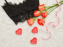 Black lace bra on the white fur, orange roses, candles. Fashionable concept. Top view. Close-up.  Stock Photos