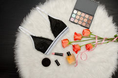 Black lace bra on the white fur. Orange roses, lipstick, perfume and eye shadow. Fashionable concept Royalty Free Stock Photography