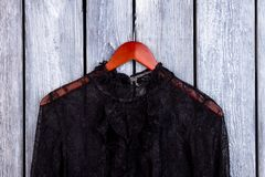 Black lace collar and hanger. Grey wooden desk surface background Royalty Free Stock Image