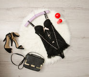 Black lace corset, shoes, handbag and red candles on a white fur. Fashionable concept Stock Photo