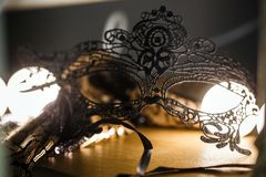 Black lace mask is on the table in a romantic atmosphere. Backlight, close-up royalty free stock photography
