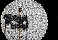 Black Lace Masquerade Mask with Silver Background. A black lace masquerade mask on bronze stand with silver and white beaded and black background royalty free stock image