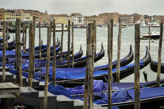 Black lacquered gondola, tied to the old wooden pier at Grand Canal, Venice Royalty Free Stock Images