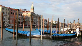 Black lacquered gondola, tied to the old wooden pier, sways with the waves at Grand Canal stock footage