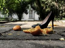 Black lacquered women shoes with heels in the street near the crushed mandarin.  stock images