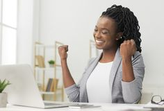 Black Lady Celebrating Business Success Sitting At Laptop In Office