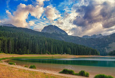 Black lake in Durmitor national park in Montenegro, Europe. Mountain, forest and beach on blue cloudy sky a sunny day at sunset. B Royalty Free Stock Image