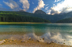 Black lake in Durmitor national park in Montenegro, Europe. Mountain, forest and beach on blue cloudy sky a sunny day at sunset. B Stock Image