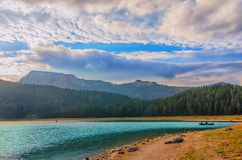 Black lake in Durmitor national park in Montenegro, Europe. Mountain, forest and beach on blue cloudy sky a sunny day at sunset. B Stock Photos