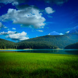 Black lake and grass near by mountians Stock Photo
