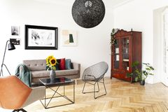 Black lamp above armchair and table in bright living room interior with poster and plants. Real photo stock photography