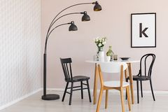 Black lamp above chairs and wooden table with flowers in dining room interior with poster. Real photo stock images