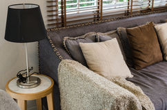 Black lamp with blanket and pillows on sofa Royalty Free Stock Image