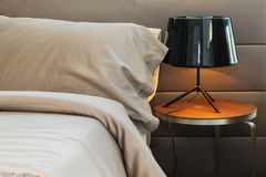 Black lamp and brown pillow on bed Stock Photo