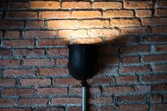 Black lamp with light on brick wall texture. stock photo