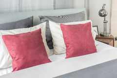 Black lamp  in modern bedroom design with red pillows. On bed Stock Photography
