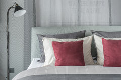 Black lamp  in modern bedroom design with red pillows. On bed Royalty Free Stock Image