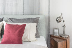 Black lamp  in modern bedroom design with red pillows. On bed Royalty Free Stock Photos